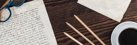 memorabilia: Close-up of an antique letter on a dark wooden table, next to coffee and pencils