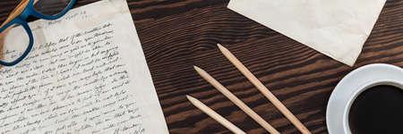lapiz y papel: Primer plano de una carta antiguo en una mesa de madera oscura, junto al café y lápices