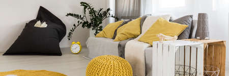 amenities: Room area with yellow pillows on a couch, pouf and coffee table made by wooden chest Stock Photo