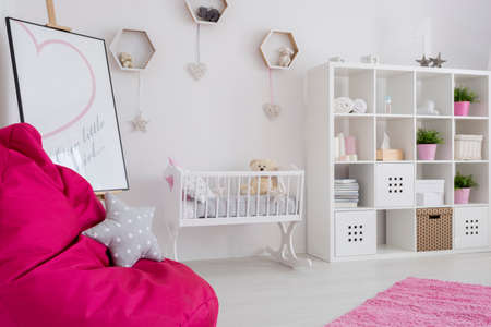 bean bag: Baby girl room in pastel colors with a book case, baby cradle, easel, and bean bag pink chair with star cushion