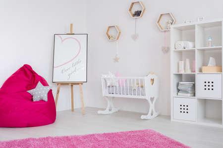 colores pastel: habitación del bebé en colores pastel, con una estantería, cuna, caballete, puf y la alfombra de color rosa Foto de archivo