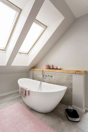 free standing: Beautiful attic bathroom design with free standing bath