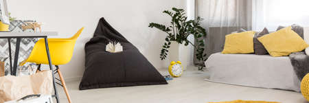 bean bag: Minimalistic room with yellow armchair standing at the desk and bean bag chair