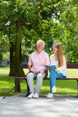 Young carer reading a book, sitting on a park bench with a senior man Stock Photo