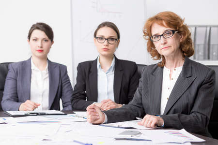 Three Formally Dressed Woman Sitting By A Desk Full Of Scattered