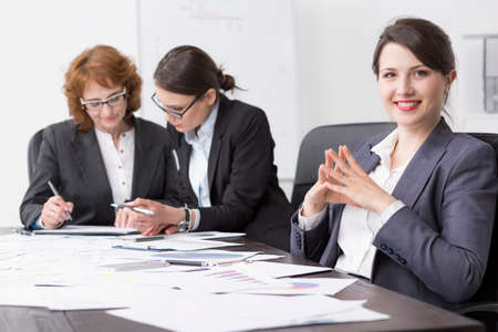 businesslike: Smiling and relaxed young office worker at a desk, with her colleagues working in the background