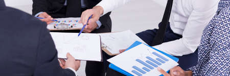 Junge Mitarbeiter sitzen nah einander und Analyse der Berichte Standard-Bild - 62140704