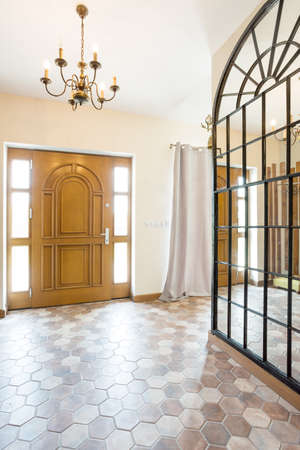 mirror on wall: Spacious corridor with big mirror on the wall, wooden entry door and a chandelier