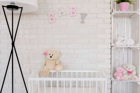 Teddy bear assis sur un berceau de bébé près de la lampe et le boîtier fabriqué par des coffres en bois sur une brique mur blanc fond Banque d'images