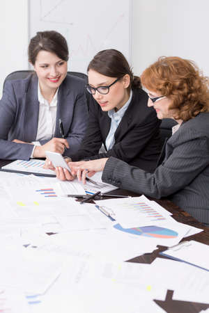 businesslike: Three female colleagues at the office, looking at a mobile phone at a desk filled with papers and documents Stock Photo