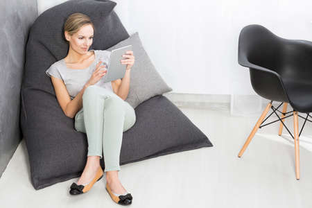 bean bag: Young woman sitting with the tablet on a bean bag chair in her modern office