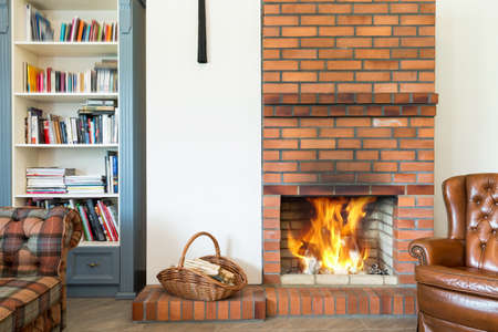 Spacious living room interior in cottage style with leather armchair, fireplace, and a book case