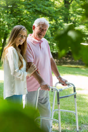Happy young carer and senior man with a walker spending time in a park