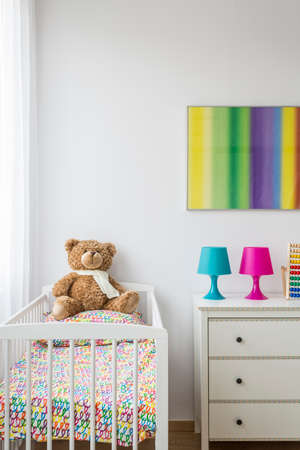 amenities: Bright infant room with baby cradle with brown teddy bear in Stock Photo