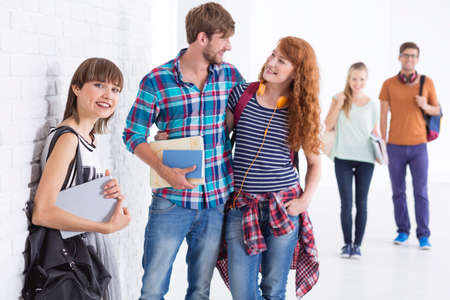 clasping: Young student clasping his girlfriend at the corridor with other students Stock Photo