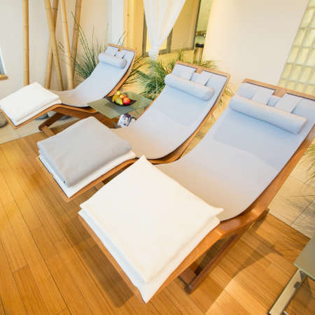 restful: Wooden comfortable sunbeds in restful room