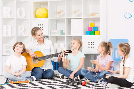 Group of children playing different musical instruments, sitting on a carpet around their smiling teacher