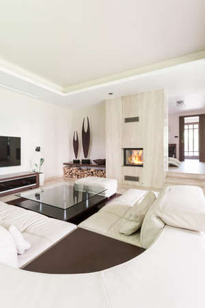 travertine: Splendid living room with a large leather lounge, travertine fireplace and decorative sculptures Stock Photo