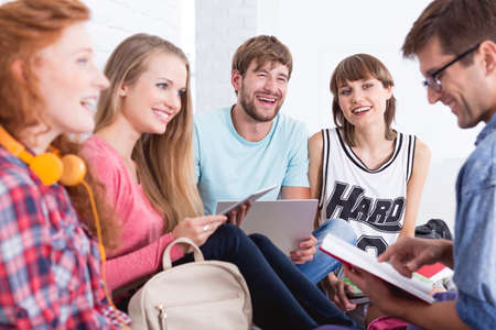 coed: Group of smiled students sitting together and doing a common revision