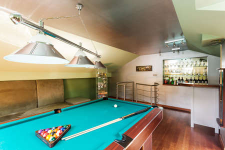 pool rooms: Close-up of a snooker table in an attic room with a home drink bar