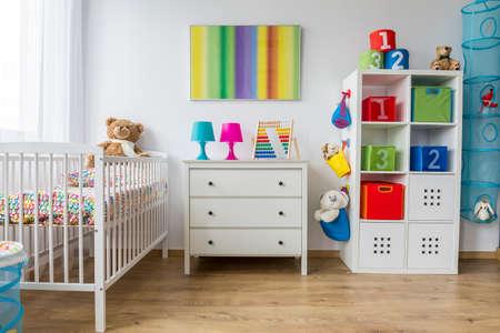 Lichte interieur van een kleurrijke babykamer met een cradle Stockfoto
