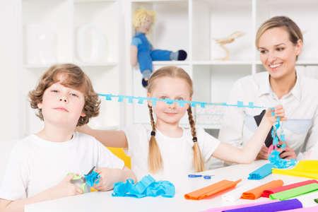 niños en edad escolar optimistas formas de corte de papel secante durante las clases de arte, junto con su profesor Foto de archivo
