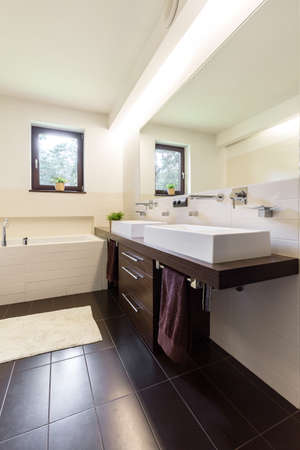 double sink: Contemporary bathroom with brown and creamy tiles and two ceramic sinks