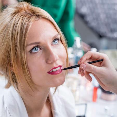 Artists hand putting lipstick during wedding makeup