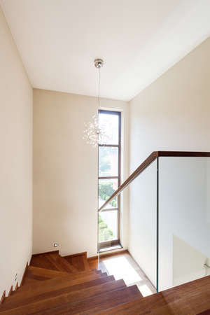 banister: Shot of stairway in a modern house, with wooden steps and glass banister Stock Photo