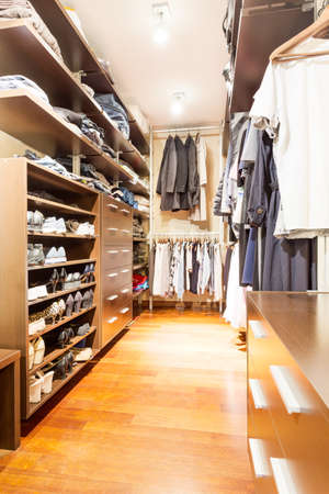 commodious: Commodious closet with shelves and drawers filled with clothes and shoes