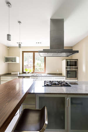 cooktop: Spacious and minimalist kitchen with marble kitchen top and chrome eave