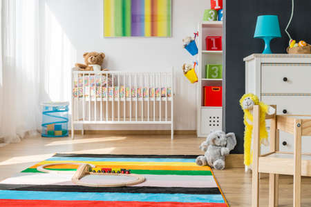 soft toys: Bright baby room with cradle and playing area with soft toys