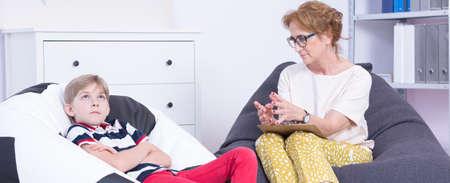 futbol infantil: colegial ansioso durante una sesión de terapia con un psicólogo de mediana edad Foto de archivo
