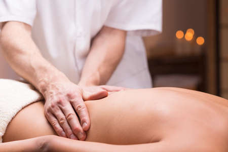 performed: Close-up of a back massage performed on a dark-skinned person Stock Photo