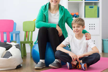 posture correction: Shot of a little boy sitting on a mat next to his trainer