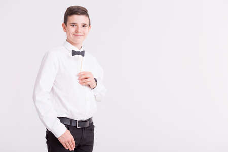 grandkid: Shot of a young boy looking at a camera while holding a paper bow tie on a stick
