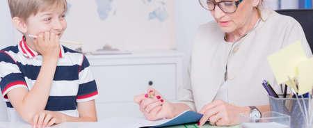 tarea escolar: De mediana edad tutor revisar la tarea de su pupila en una habitación luminosa