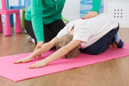posture correction: Shot of a little boy stretching on an exercise mat and his physiotherapist helping him