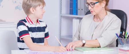 tutor: estudiante por escrito algo optimista con la ayuda de su tutor de mediana edad