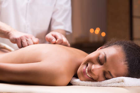 Smiling dark-skinned woman receiving a back massage