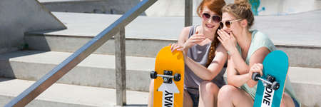 bff: Two skater girls sitting on a city stairs with their skateboards during summer day, panorama Stock Photo
