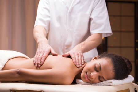Relaxed dark-skinned woman undergoing a back massage Stock Photo