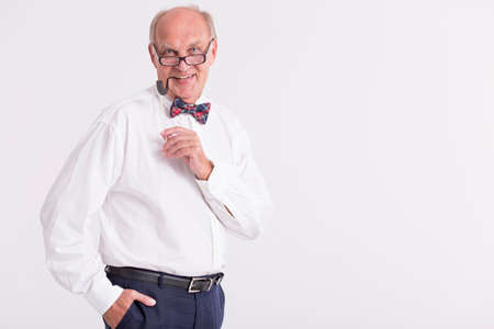 Portrait of a man with a bow tie holding a paper pipe on a stick Stock Photo