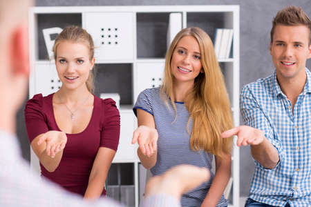 Three young people holding their hands in to give hand gesture Banco de Imagens