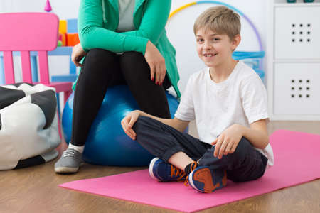 posture correction: Shot of a little boy sitting on an exercise mat and his trainer sitting next to him Stock Photo