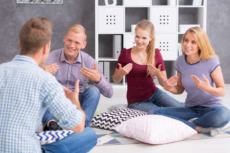 Group of three young people and a man teaching them a sign language Stock Photo