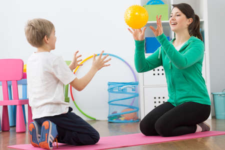 posture correction: Shot of a little boy and his physiotherapist playing with a ball