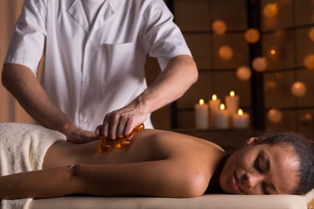 Therapist using a massage device during a young womans back massage Stock Photo