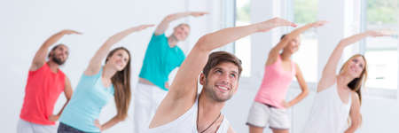 sports training: Group of active people doing physical exercises during professional classes, panorama