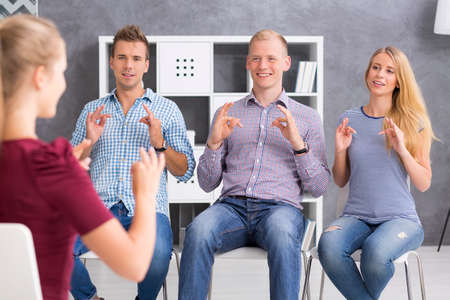 languages: Grupo de jóvenes aprenden una lengua de signos Foto de archivo